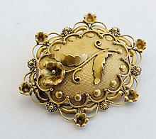 An ornate 19thC gilt metal brooch of oval form with floral