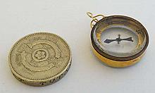 A gilt metal pendant / fob formed compass within a 9ct gold