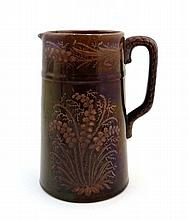 A 19thC red lustred pottery jug with Lily of the