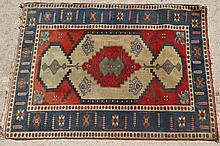 Rug / Carpet: a mid 20thC Hand made woollen rug with red ground, central gr