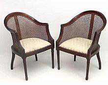 A pair of early 20thC walnut caned single armchairs standing on four legs w