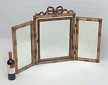 An early 20thC folding tryptic mirror with gilded reeded column, lions mask