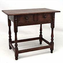 A 20thC oak side table with frieze drawer sliding on side hangers with carv