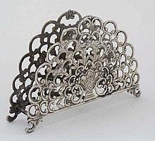 A white metal letter rack / napkin holder with floral and C scroll decorati