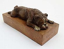 A 21stC cold painted bronze model of a boxer dog recumbent upon a rouge mar