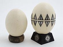 Two ostrich eggs one with applied decoration and approx 8'' high ( includin