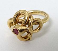A gold ring formed as a coiled snake with inset ruby to head.