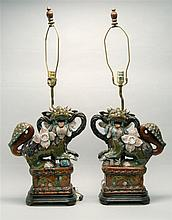 PAIR OF POTTERY FU LIONS Depicted standing on rectangular platforms. Mounted as table lamps. Heights of lions 16.25