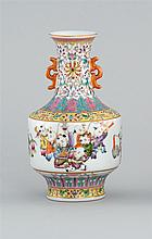FAMILLE ROSE PORCELAIN VASE In baluster form with openwork handles and decoration of children at play. Six-character Qianlong mark o...