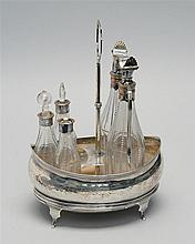 GEORGIAN SILVER BRIGHT-CUT CASTER SET Includes oval stand and five cut and faceted bottles with silvered mounts. Height 10