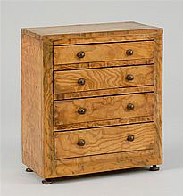 MINIATURE CHEST In heavily figured wood veneers. Four graduated drawers and turned wooden feet. Height 12.75