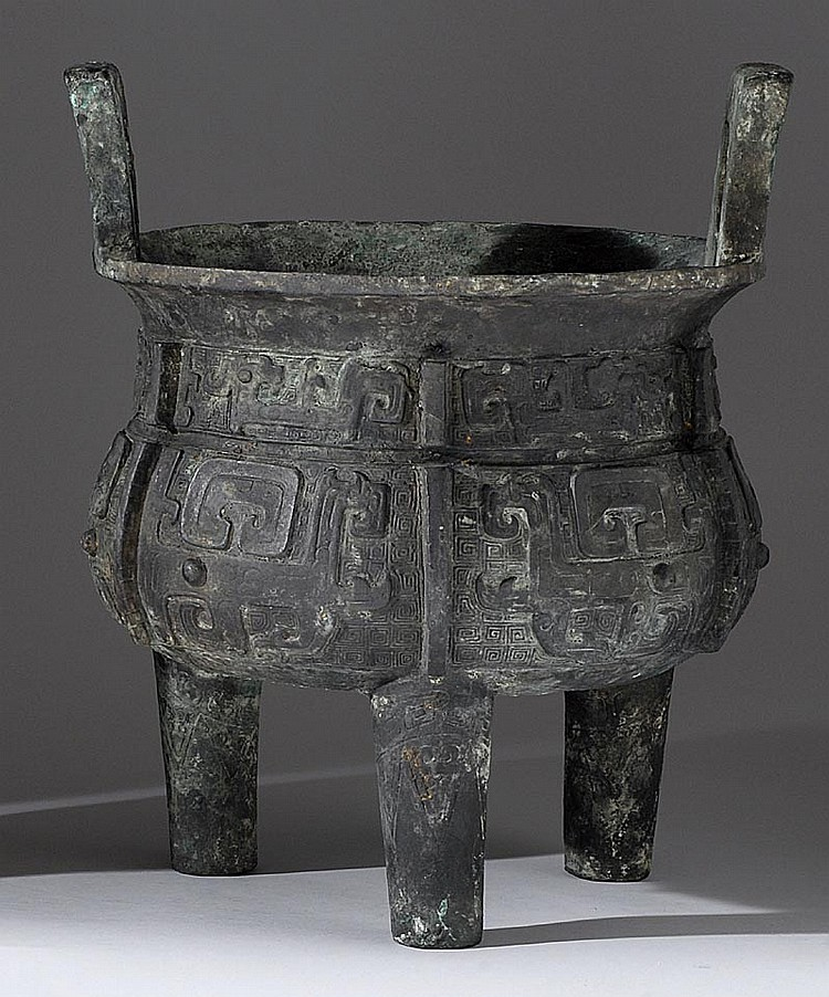 BRONZE DING In Shang style with tripod base, rectangular handles, and archaic mask-style decoration. Diameter 11½