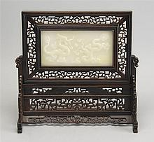 WHITE HARDSTONE TABLE SCREEN In rectangular form with carved wood stand. Hardstone panel with dragon and pearl design. Panel cracked...