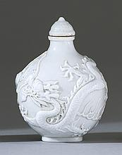 BLANC DE CHINE PORCELAIN SNUFF BOTTLE In ovoid form with relief phoenix and dragon design. Four-character Daoguang mark on base. Con...