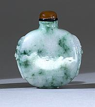 GREEN AND WHITE JADEITE SNUFF BOTTLE In flattened ovoid form with mask and mock ring handles. Height 2