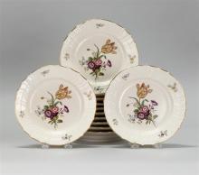 SET OF TWELVE ROYAL COPENHAGEN PORCELAIN PLATES With central transfer floral decoration and basketweave molded rims. Diameters 8