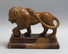 ROCKINGHAM OR TREACLE-GLAZED YELLOWWARE FIGURE OF A LION Standing lion with its left front paw resting on a sphere and its tail slun...