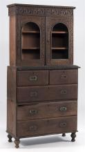 ORNATELY CARVED CABINET In mahogany and other woods. Upper section with two doors enclosing two shelves. Lower section converted fro...