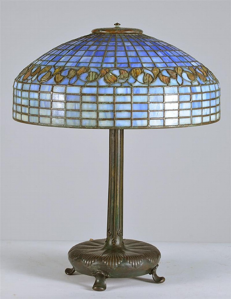 TIFFANY-STYLE LEADED GLASS TABLE LAMP with four-footed bronze base in scallop shell design. Shade is blue and green with brown leaf...