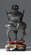 TRIPOD BRONZE CENSER With elephant's-head base, loop handles, and vajra design on finial. Height 7