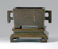 BRONZE CENSER-ON-STAND In rectangular form with raised feet and geometric handles. Four-character Ming mark on base. Length 5.1