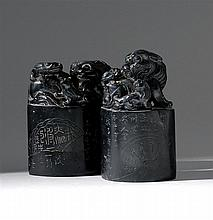 TWO BLACK HARDSTONE SEALS In oval form. With carved finials of a fu dog and her two pups resting on calligraphic bases. Bases cut wi...