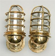 PAIR OF BRASS SHIP'S COMPANIONWAY LIGHTS With glass lenses and protective brass cages. Overall height 10