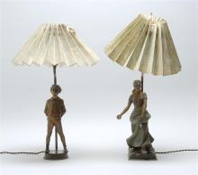 TWO POT METAL FIGURAL LAMPS One a young girl and the other a young boy. Girl with polychrome decoration of a green dress with red bo...