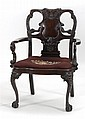 GEORGIAN-STYLE ARMCHAIR in mahogany with extensive floral and foliate-carved back and arms. Cabriole legs with satyr-form knees end...