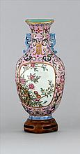 FAMILLE ROSE PORCELAIN WALL POCKET In baluster form with floral cartouche on a pink floral ground. Six-character Qianlong mark on ba...