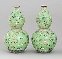PAIR OF POLYCHROME PORCELAIN VASES In double gourd form with floral design on a green ground. Six-character Daoguang mark on base. H...