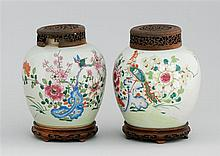 PAIR OF PORCELAIN JARS Enamel decoration of flower and birds on a white ground. With pierced wood covers and wood bases. Heights 10