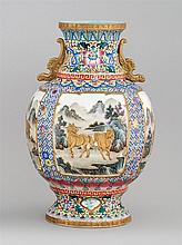 FAMILLE ROSE PORCELAIN VASE In ovoid form with flared foot and bat-form handles. Body decorated with relief cartouches of goats, wat...