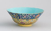 POLYCHROME PORCELAIN BOWL In double volute form with pahua design on blue and yellow ground. Six-character Qianlong mark on base. Di...