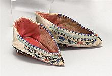 PAIR OF EMBROIDERED LOTUS SHOES A design of flowering vines on white silk; purple silk sole, red hopsack wood-covered heel. Length 3...