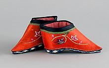 PAIR OF EMBROIDERED RED LOTUS SHOES With crewel stitchwork decoration of mandarin ducks and lotus. Soles embroidered with flowering...