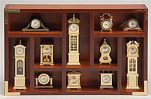 DESK-TOP DISPLAY CASE CONTAINING MINIATURE QUARTZ CLOCKS by Bulova. Includes eleven examples, three of which are tall-case. Made in...