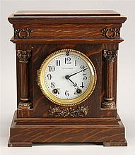 LATE 19TH CENTURY SETH THOMAS SHELF CLOCK in quarter-sawn oak case. Face flanked by two half-columns with copper mounts. Height 10¾