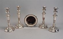 FOUR ENGLISH SILVER PLATED CANDLESTICKS in column form with ribbed, floral, and shell motifs. Heights 11