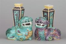 PAIR OF BISQUE AND POLYCHROME PORCELAIN JOSS STICK HOLDERS In the form of lions in green and lavender, each caparisoned with a recta...