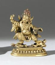 SINO-TIBETAN GILT-BRONZE FIGURE In the form of a deity dancing on two prostrate human figures, all on a lotus base. Height 3.2