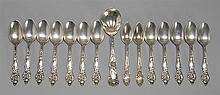 TWELVE STERLING SILVER PLACE SPOONS BY R. WALLACE & SONS In a full rose pattern. Together with a sugar shell and two citrus spoons i...