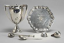 TWO STERLING SILVER TROPHIES Together with four sterling silver and silver plated tea strainers. One trophy is a Chippendale-style s...