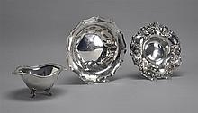 THREE STERLING SILVER BOWLS By various makers. Includes an oval candy dish supported on four paw feet, a fruit bowl with embossed fl...