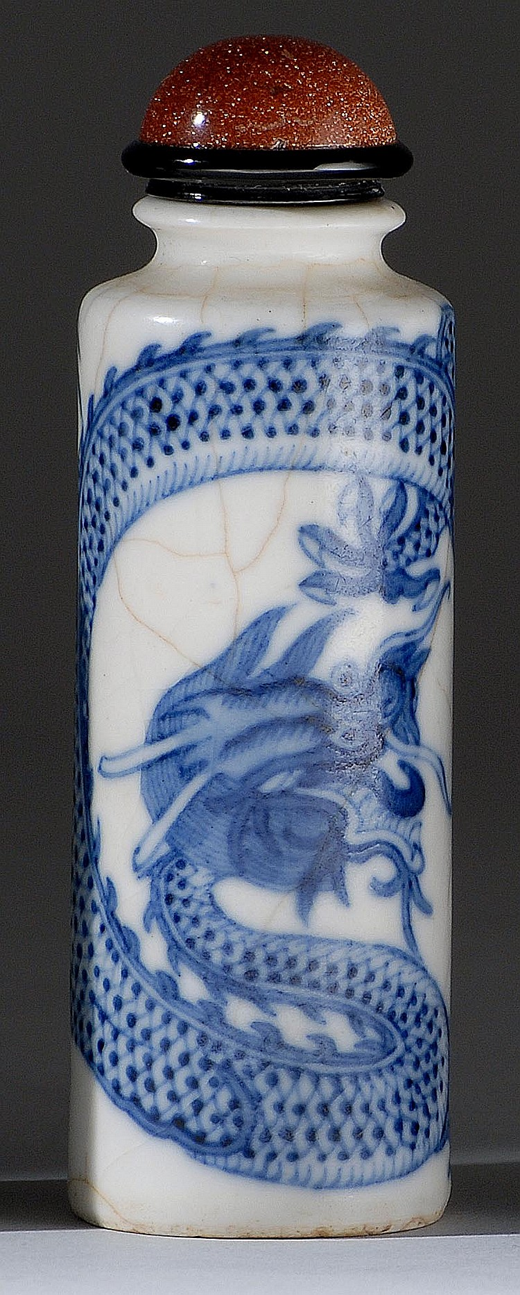 BLUE AND WHITE PORCELAIN SNUFF BOTTLE In cylinder form with decoration of dragon and pearl. Base with qilin design. Considerable cra...