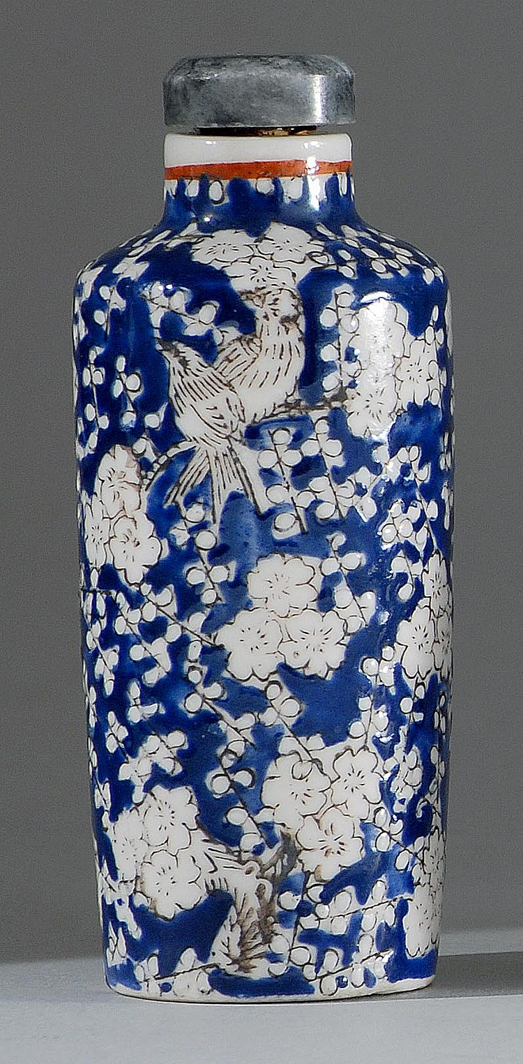 PORCELAIN SNUFF BOTTLE In cylinder form with mockingbird and prunus design in black, white, and blue. Height 2¾