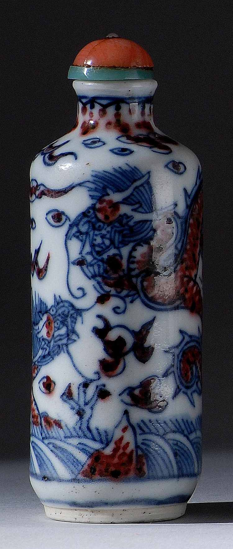 UNDERGLAZE RED AND BLUE PORCELAIN SNUFF BOTTLE In cylinder form with dramatic depiction of two dragons and waves. Height 3