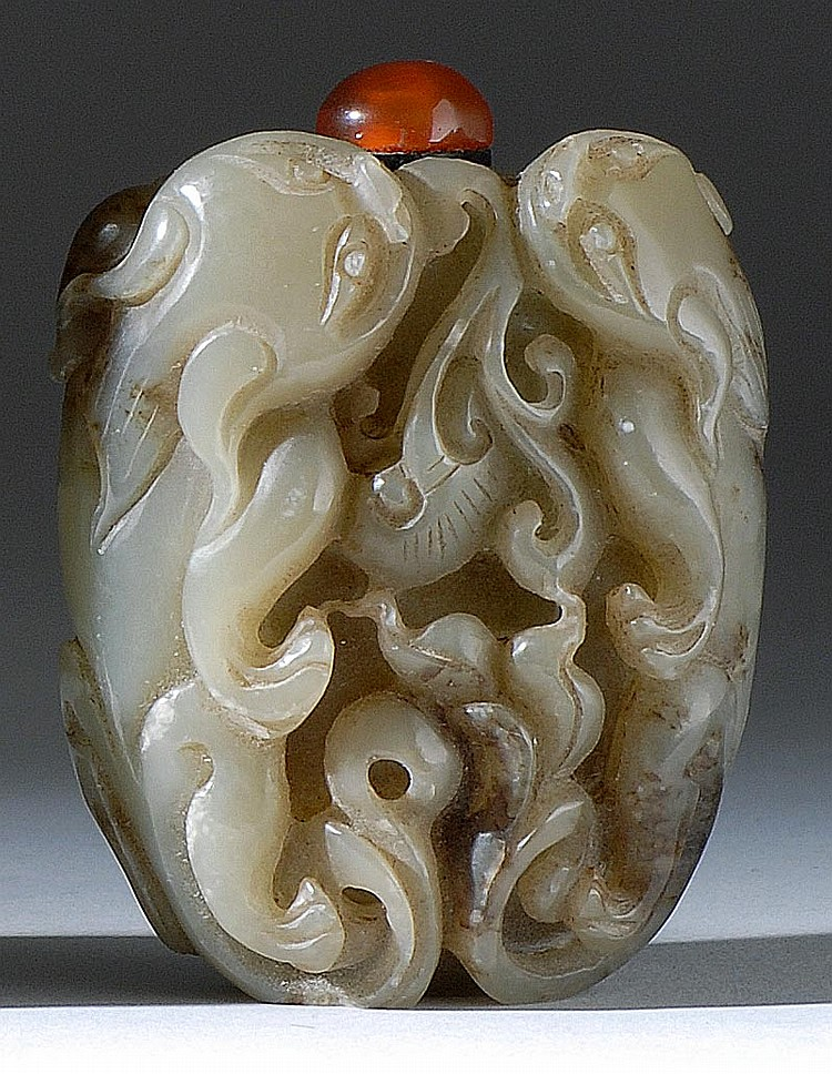 CELADON JADE SNUFF BOTTLE Carved with qilong dragons and ruyi fungus. Height 2¼