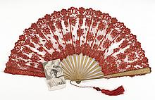 ALLEN-TYPE LILLIAN RUSSELL FAN Red lace netting with gold sequins applied to tan-painted wood sticks with gold-painted dots. Brass r...