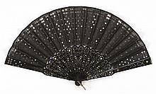 SILK NETTING AND WOOD FOLDING FAN Silver sequins applied extensively to black netting leaf. Pierced black wood sticks and guards inl...
